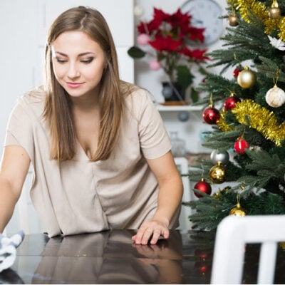girl cleaning and polishing table with christmas tree in background FEATURED