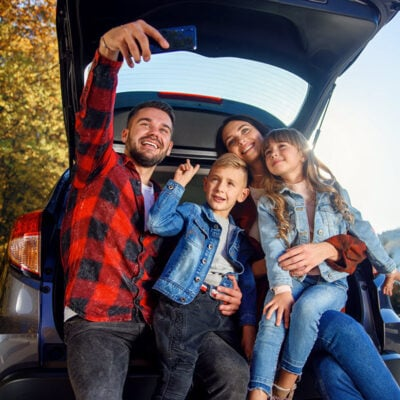 happy-stylish-parents-with-their-cute-lovely-children-are-making-funny-selfie-smart-phone-while-sitting-trunk-happy-modern-family-concept FEATURED