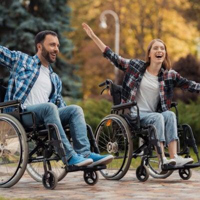 man-woman-wheelchairs-ride-around-park