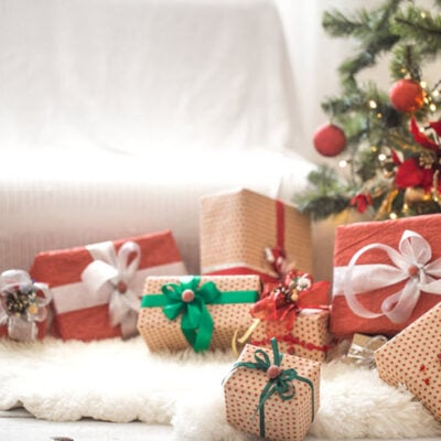 pile-christmas-presents-light-wall-wooden-table-with-cozy-rug-christmas-decorations FEATURED