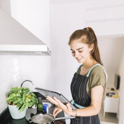 smiling-woman-preparing-food-holding-digital-tablet