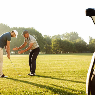 young-sportsman-practicing-golf-with-his-teacher-featured